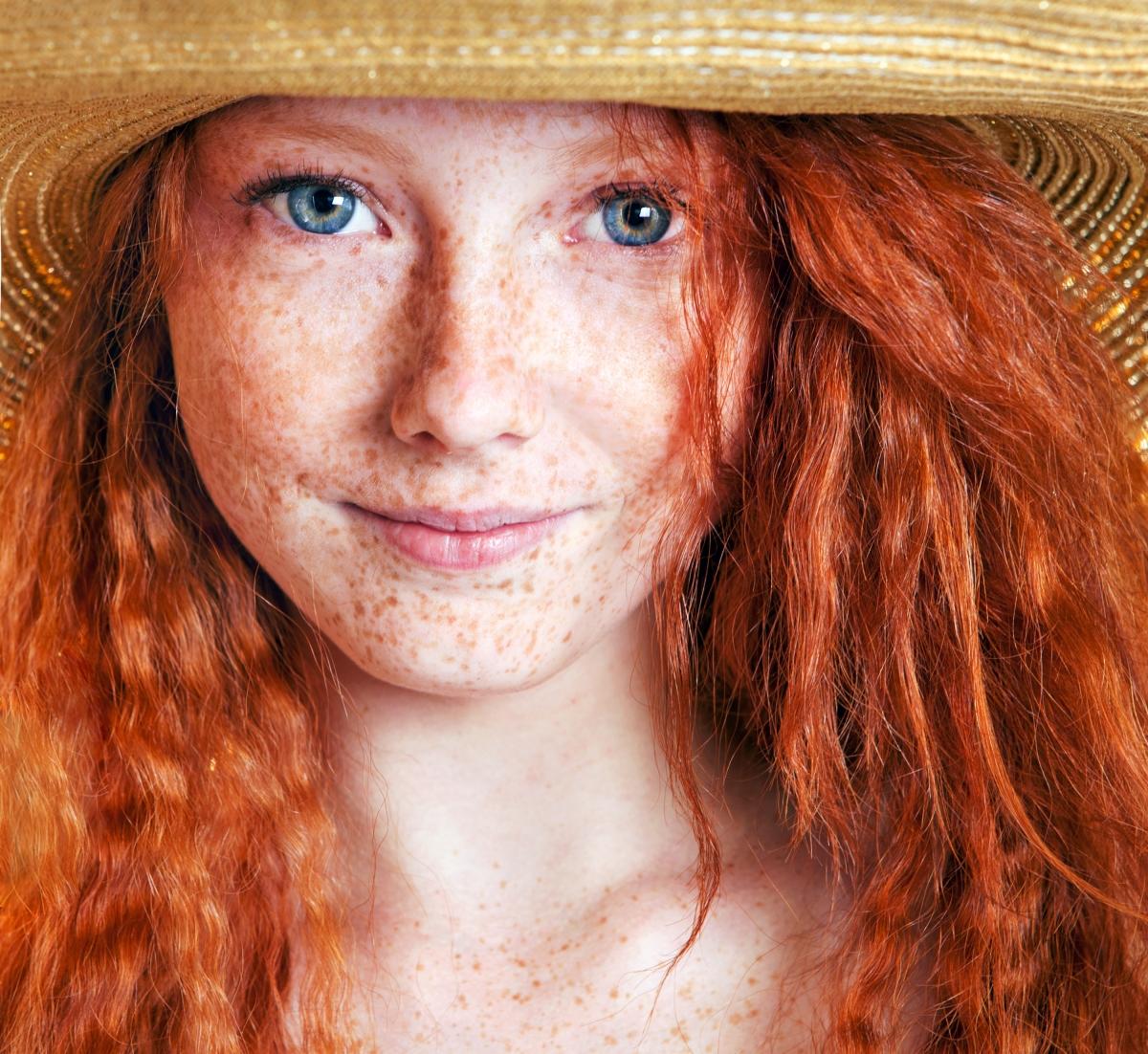 Portret van meisje met sproeten en rood haar. Het meisje draagt een strooien hoed.
