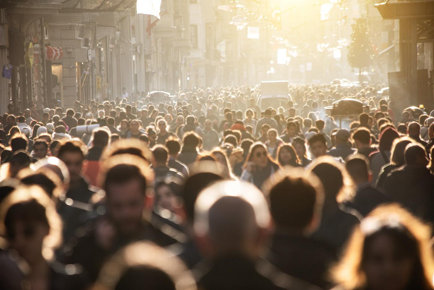 Een grote hoeveelheid mensen die in een winkelstraat lopen. De foto is genomen in tegenlicht.