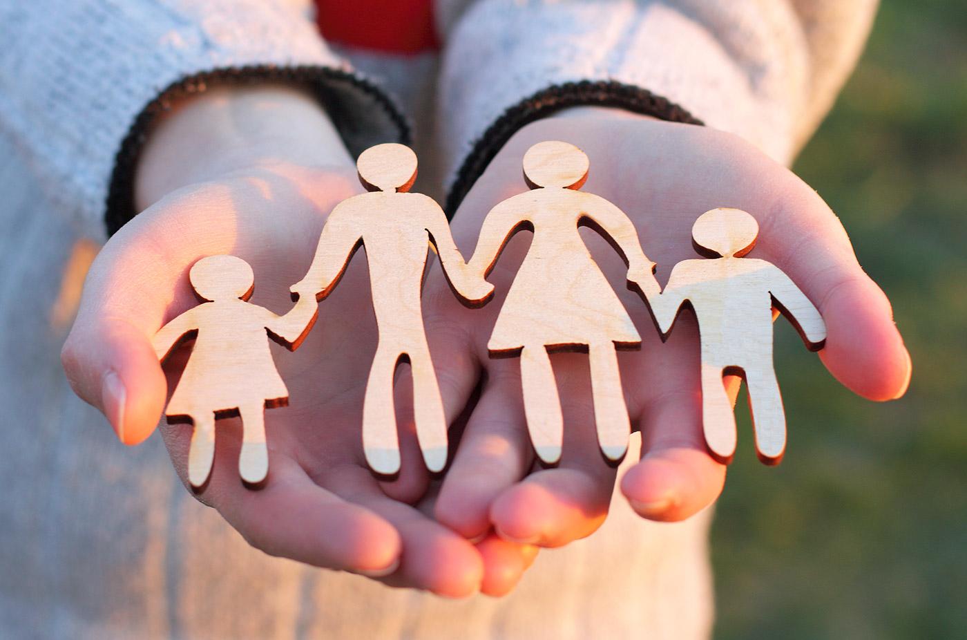 Kinderhanden houden gefiguurzaagde triplex afbeelding van een vader en met een moeder met links en rechts een kind. De vier figuurtjes houden elkaars hand vast.